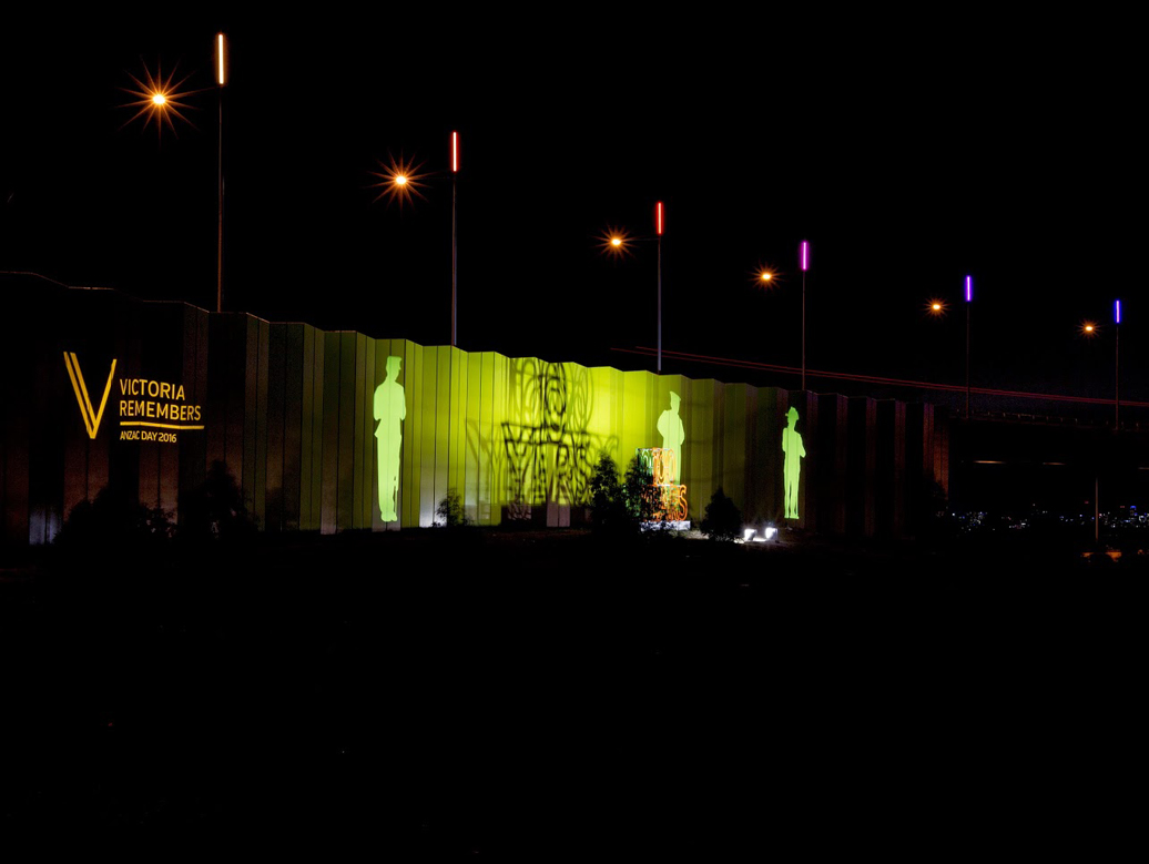 Anzac soldier silhouettes projected onto highway facade