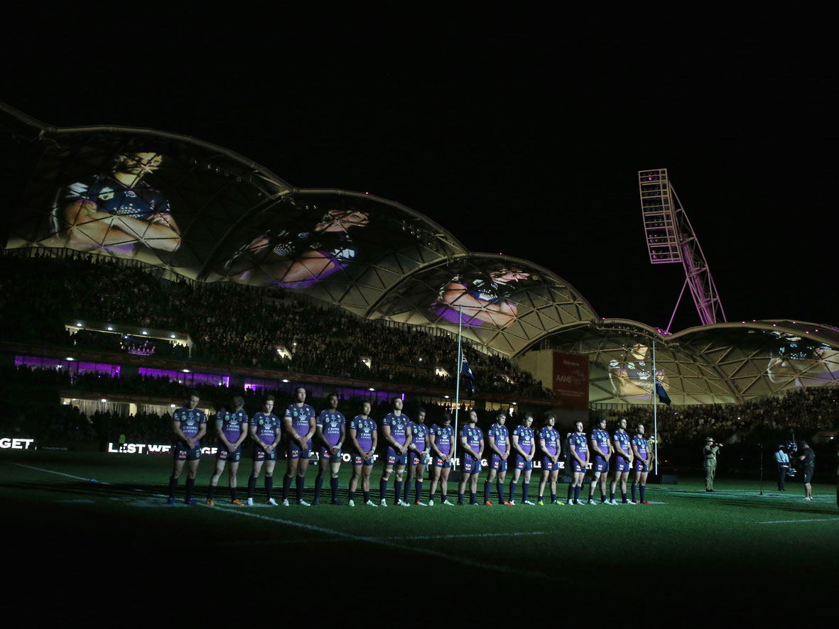 Melbourne Storm players standing for Australian anthem featuring full colour play gobo projections